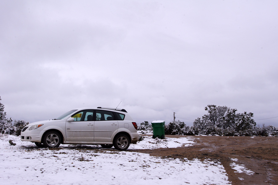 Car parked on a muddy, snowy road in Taos