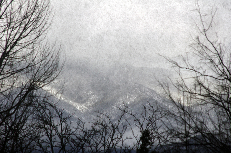 mountainside in snow through dirty window
