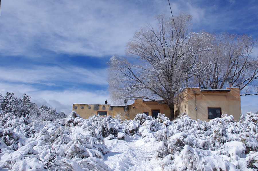 old adobe on a snowy hillside in Taos, NM